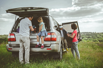 Cheerful father and daughter are taking baggage from the car trunk. Mother is helping her son to going out the transport. Happy vacation on meadow concept