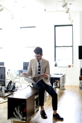 Businessman reading newspaper while sitting on desk in office
