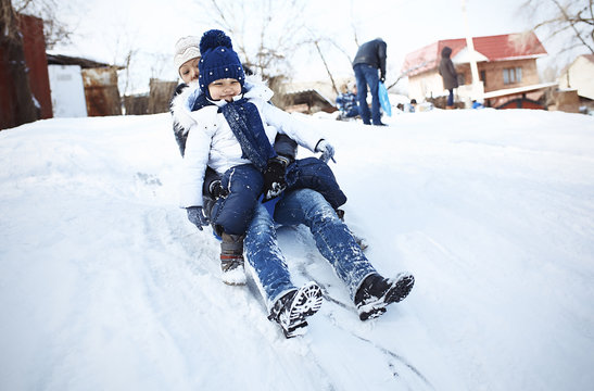 Excited mother and daughter tobogganing on snowy field