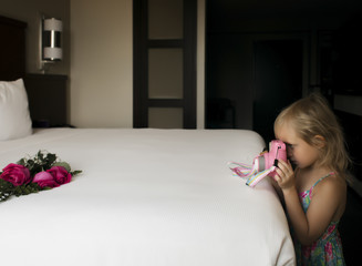 Side view of girl photographing roses on bed at home