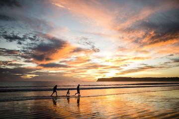 Silhouette parents with son running at beach against cloudy sky during sunset