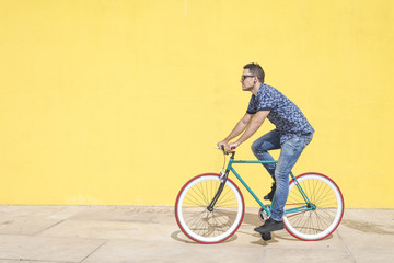 Full length of man riding bicycle against yellow wall at sidewalk in city