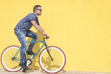 Man riding bicycle against yellow wall at sidewalk in city
