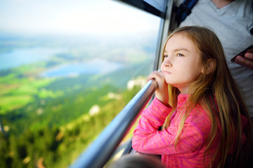 Cute little girl having a cableway ride to Tegelberg mountain, a part of Ammergau Alps, located nead Fussen town, Germany.
