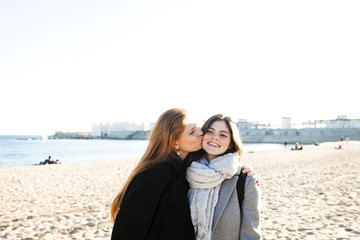 Loving mother kissing daughter while standing against clear sky at beach