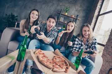 Who will be the winner? Four cheerful excited joyful delightful crazy gamers spending time together eating takeaway food drinking deer on couch at home