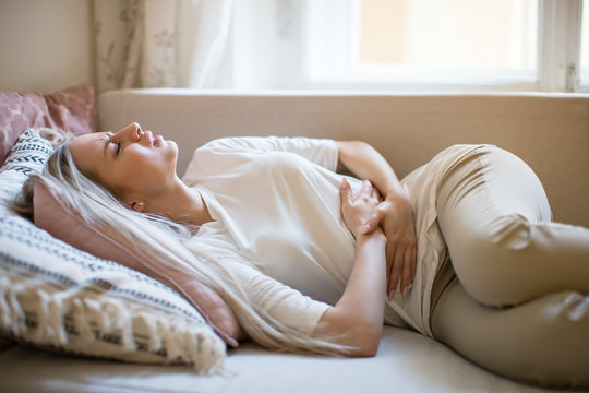 Health issues problems. Young woman suffering from stomach pain, feeling abdominal pain or cramps, lying on sofa. Period menstruation, women health problem, food poisoning