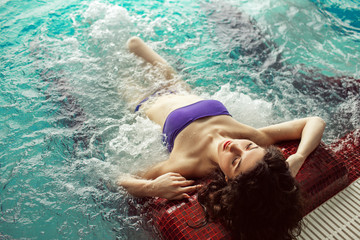 Pretty young woman is relaxing in jacuzzi bath tube in spa complex, health resort concept
