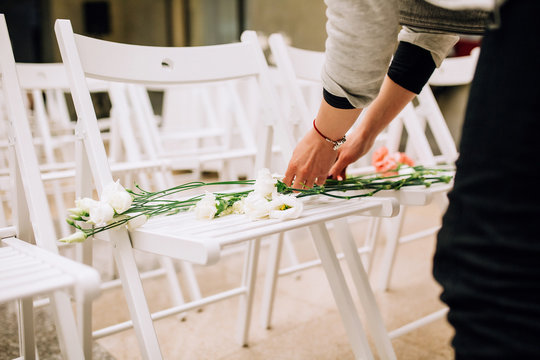 girl florist in a gray jacket laying flowers on white chairs