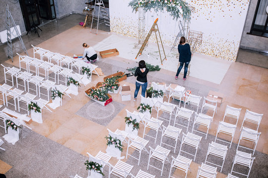 the process of preparation by florists and decorators of the hall for the wedding ceremony