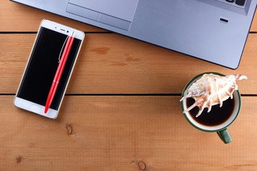 Laptop and cup of coffee on a wooden background, workstation on an old desk, smartphone and a notebook, pen and glasses in the workplace, designer workstation, art