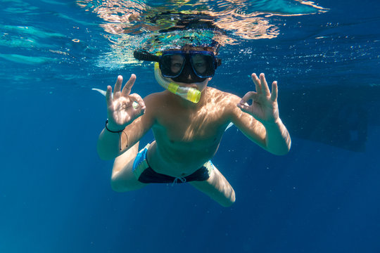 Boy in swimming mask dive in Red sea near yacht