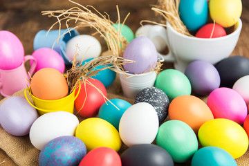 Multi-colored Easter eggs in nest on wooden background, selective focus image. Happy Easter card