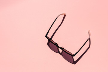 High angle view of women's tinted glasses on pink background with hard shadows from bright sunlight (selective focus)