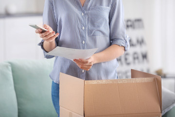Young woman making call about delivered parcel at home