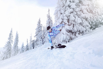 Snowboarder on ski piste at snowy resort. Winter vacation