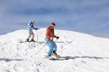 Tourists on ski piste at snowy resort. Winter vacation