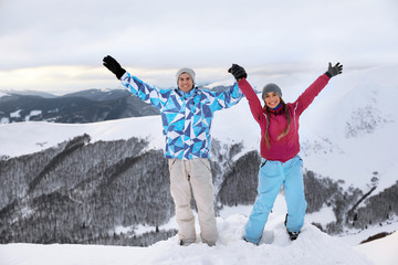 Happy couple on snowy mountain peak at resort. Winter vacation