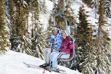 Happy couple on ski lift at snowy resort. Winter vacation