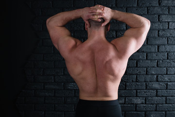 young strong bodybuilder posing near the old brick wall. part of body: the broad back and muscular male ass. bald head guy in tights. athletic figure after exercise and diet