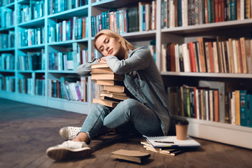 White girl near bookshelf in library. Student is sleeping with books on her lap.