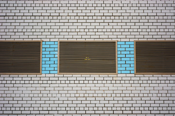 Wall of cooperative building for store, workshop, garage and other industrial needs. Background from white brick wall with metallic closed windows and insertions of blue brick close-up.