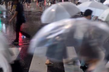エモい雨の夜のスクランブル交差点を行き交う人々。現代の忙しなさイメージ。動き、ぶれ演出