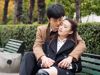 Portrait of couple of Chinese young people sit in bench in autumn park, hand in hand and hug together, lover concept.