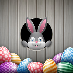 Cute Easter bunny peeking out of a hole with colorful eggs