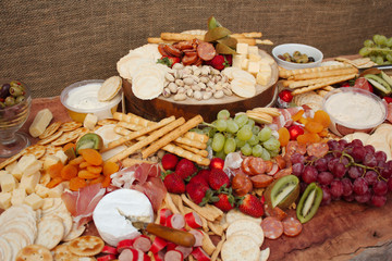 A Delicious Food Platter of Fruit, Nuts, Chesse, Dips, Deli Meats and crackers.