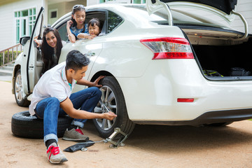 Father change a new tire but mother and daughter wait in car