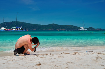 Guy takes pictures on the beach, kneeling. Sea bay with turquoise water under bright blue sky landscape background. Copy space.