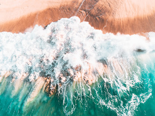 Aerial view of colorful waves crashing in sea