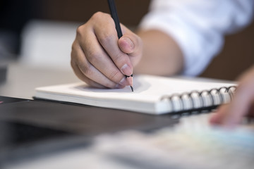 Close up view image of man writing on notebook while working at office