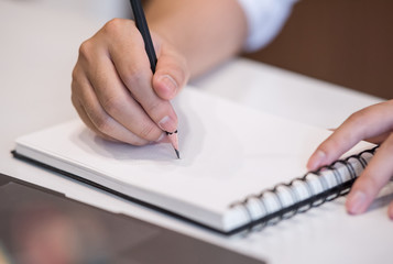 Cropped image of man writing on notebook while working at office