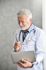 Senior male Doctor is thinking and checking his patient medical records on a laptop computer in the Medical room. Serious. Technology.