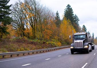 Black big rig semi truck transporting tank semi trailer driving on wide autumn highway