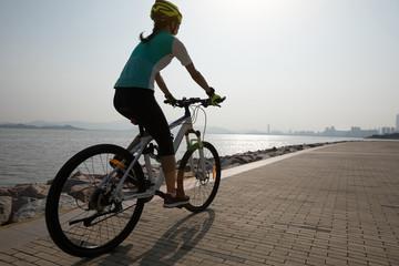 female cyclist riding mountain bike on seaside