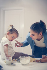 Mother and daughter playing in kitchen and baking cookie.
