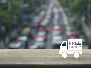 Free delivery truck icon on wooden table over blur of rush hour with cars and road, Transportation business concept