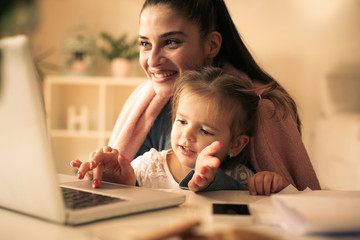 Single mother and little girl at home using laptop.