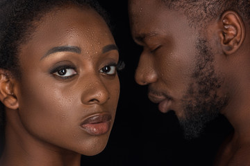 beautiful african american couple with water drops on faces posing isolated on black