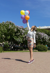 girl in short dress holding lots of colorful balloons in the Park, lilac bushes, Sunny day