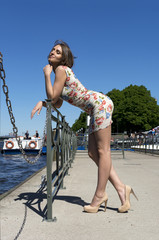 leggy girl in short dress stands on the riverfront on a Sunny day, portrait of a young woman