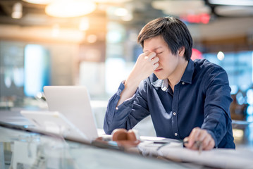 Young Asian business man feeling stressed and frustrated while working with laptop computer. Male entrepreneur getting in trouble with his job. freelance lifestyle in urban workspace.