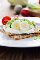 Chia seed crackers with cream cheese, cucumbers, tomato, quail egg and green onion