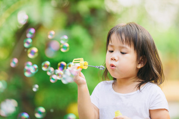 Outdoors activity : Cute kid blowing bubbles soap in the  garden. Picture for concept of childhood in school age.