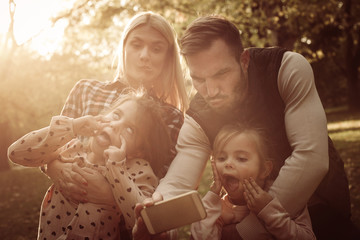 Father taking self picture of family in meadow.
