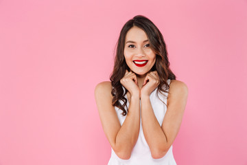 Image of asian adorable woman with dark curly hair in white dress holding arms on chest and looking straight with perfect smile, isolated over pink background