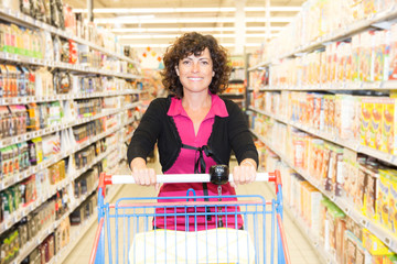 image of woman pushing trolley in aisle in supermarket